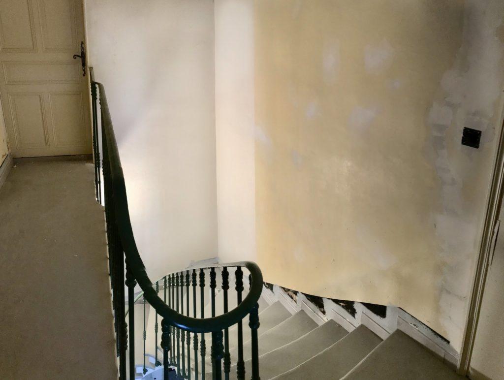 Travail minutieux de la pose d'une toile de verre pour rattraper un escalier fissuré.